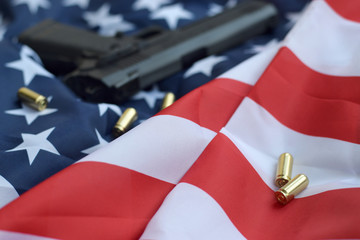 9mm bullets and pistol lie on folded United States flag