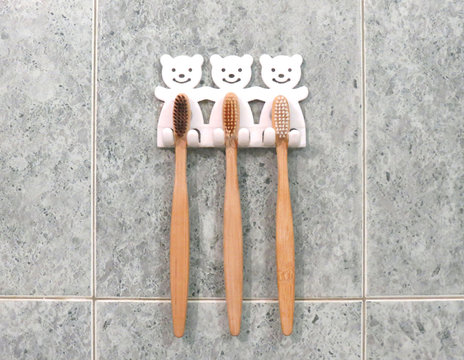 A family set of three bamboo toothbrushes hang on the bathroom's wall in toothbrush holder. Ecological lifestyle.
