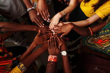 Hands of happy group of multinational African, latin american and european people which stay together in circle