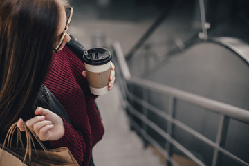 Young pretty woman blogger with smartphone, cup of coffee and shopping bags in city mall