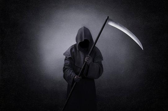 Grim reaper with scythe in the dark