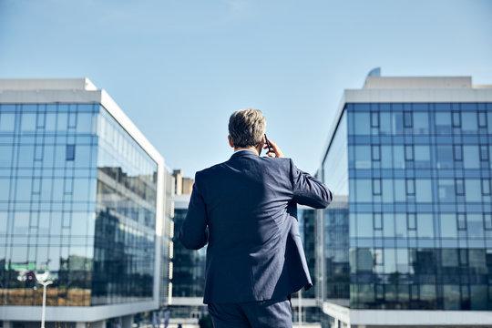 senior businessman office building mobile phone outdoor city