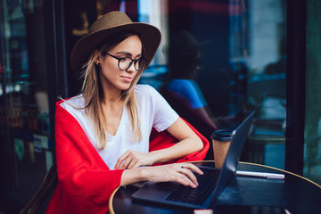 Trendy blogger typing on laptop at cafe table