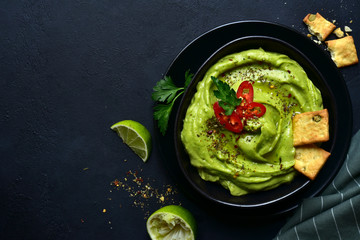 Guacamole - traditional mexican spicy avocado dip. Top view with copy space.