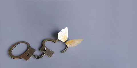 Conceptual picture of the separation or divorce of spouses or lovers. Background, banner with open handcuffs and a flying butterfly. The criminal is released from prison.