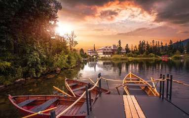 Tuinposter Bergen amazing mountains lake in Europe - Strbske pleco, summer sunset, boats near coast on background golden evening sunlight, scenic nature view, Slovakia, High Tatras, discover yourself beauty world