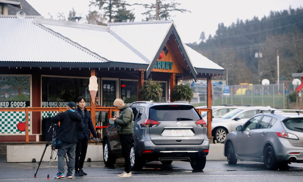 Members of the news media wait outside the the Deep Cove market near the property where Prince Harry and Meghan are believed to be staying in North Saanich