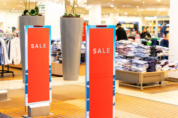 Red bright sale word banner on anti-thieft gate sensor at retail shopping mall entrance. Seasonal discount offer in store