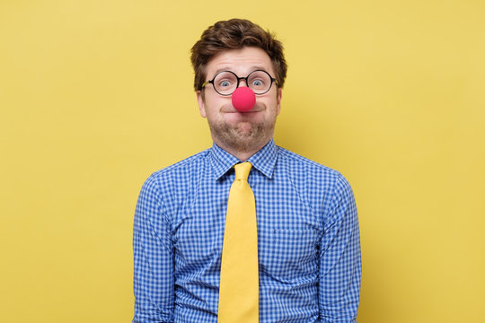 Young handsome man with red clown nose blowing cheeks.
