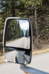 Vertical shot of a car side mirror reflecting the road in the middle of the trees in Canada