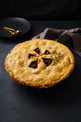 Fruit pie with plums and thyme on dark blue background