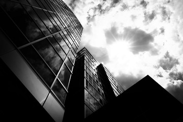 Fotobehang Oude gebouw Low angle grayscale shot of business buildings with a cloudy sky in the background