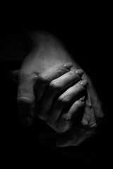 Vertical romantic shot of a couple holding hands on a black background