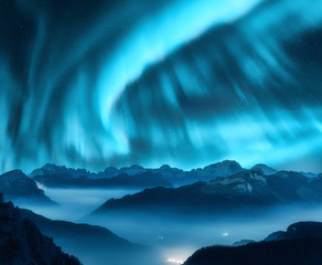 Tuinposter Noorderlicht Aurora borealis above the mountains in fog at night. Northern lights. Sky with stars with polar lights and high rocks. Beautiful landscape with aurora, city lights in low clouds, mountain peaks. Space