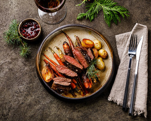 Grilled sliced Venison Steak with baked vegetables and berry sauce and Red wine on dark background