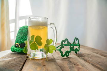 St. Patricks Day green shamrocks with a full cold frosty glass of beer   background