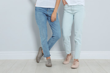 Young women in stylish jeans near light wall, closeup Wall mural