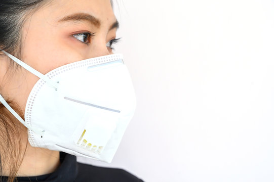 Close up of young Asian woman wearing N95 mask for protect smog PM2.5 bad air pollution. Air pollution has been associated with diseases of the heart and lungs, cancers and other health problems.