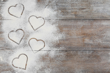 Heart shapes made of flour on wooden table, top view. Space for text