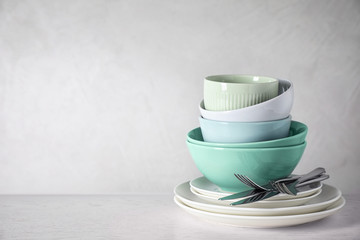 Set of clean dishware on white table. Space for text