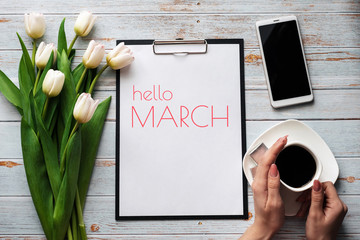 Greeting card with the inscription Hello March. Bouquet of white Tulip flowers with a Cup of coffee and a smartphone Wall mural