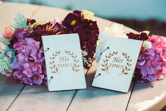 Selective focus shot of wedding vows placed next to beautiful flowers
