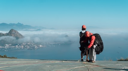 People getting ready to sky glide in Rio de Janeiro under the beautiful blue sky
