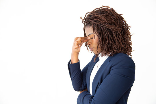 Stressed young businesswoman with closed eyes. Side view of tired young businesswoman rubbing nose bridge isolated on white background. Stress concept