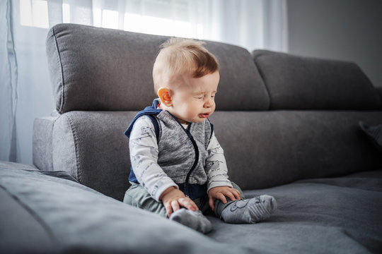 Adorable little boy sitting on couch in living room and sneezing.