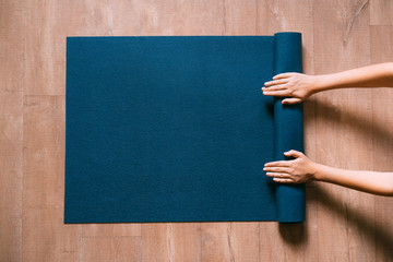 Fit woman folding blue exercise mat on wooden floor before or after working out in yoga studio or at home. Equipment for fitness, pilates or yoga, well being concept. Flat lay, space for text. Wall mural