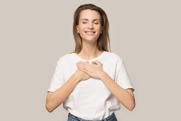 Happy grateful woman hold hands at chest feeling thankful