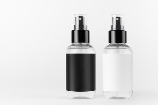Two transparent spray bottles for cosmetics product with black, white blank labels on white background, mock up for branding, advertising, design.