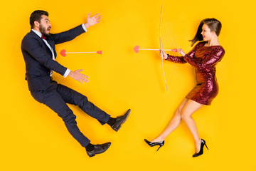 Top above high angle full body profile side photo two people cupid girl shoot arrow shocked man fall love hunter hunt concept wear red short dress tux suit lay isolated yellow color background