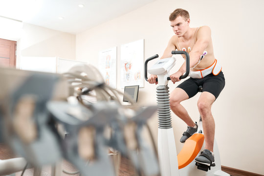 Man patient, pedaling on a bicycle ergometer stress test system for the function of heart checked. Athlete does a cardiac stress test in a medical study, monitored by the doctor.