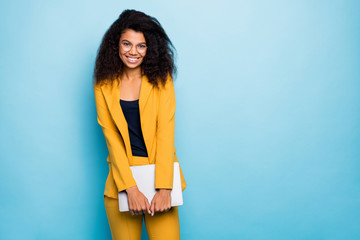 Photo of pretty dark skin wavy business lady holding notebook friendly work atmosphere visit corporate training wear specs yellow suit blazer pants isolated blue color background Fotobehang