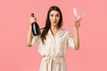 Shall we. Cheerful and excited girl want celebrate great news, open bottle champagne and folding lips showing tempting suggestion, holding two glasses, want drink together, pink background