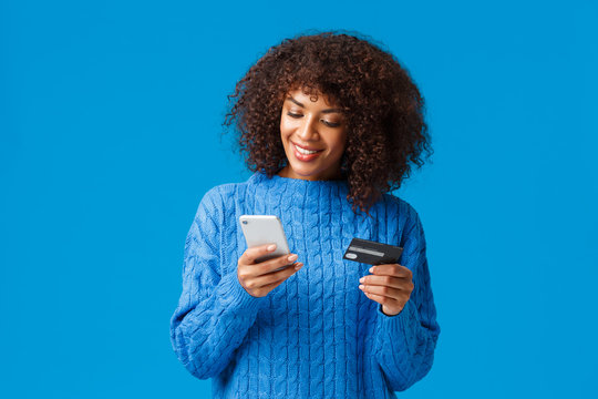 Shopping, holidays and presents concept. Attractive smiling african-american woman paying for online purchase, buying gifts in internet, holding credit card and smartphone, submit payment