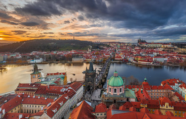 Foto op Aluminium Praag Prague, Czech Republic - Aerial panoramic drone view of the world famous Charles Bridge (Karluv most) and St. Francis Of Assisi Church with a beautiful winter sunset. St. Vitus Cathedral at background