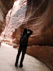 Estrecho cañón de rocas rojas con turista sacando fotos