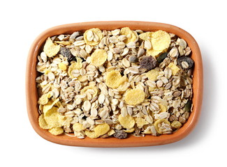 Muesli mixture of wholegrain foods, cereals, seeds and raisins in clay bowl isolated on white background, top view