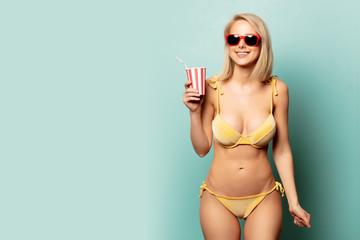 Beautiful blonde woman in bikini with paper cup