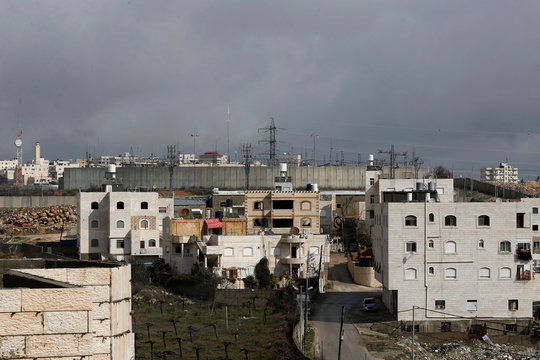 A view shows Palestinian houses as an Israeli power distribution plant is seen in the background in Hebron in the Israeli-occupied West Bank