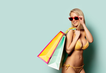 Beautiful blonde woman in bikini with shopping bags