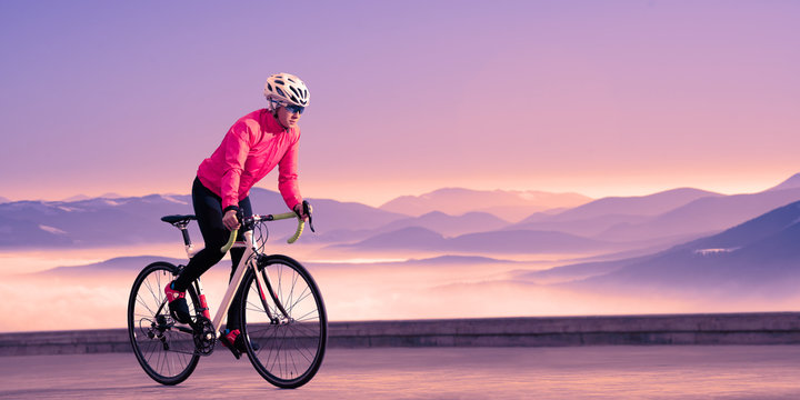 Young Woman Cyclist Riding Road Bike in the Beautiful Mountains at Purple Sunset. Adventure, Healthy Lifestyle, Sport