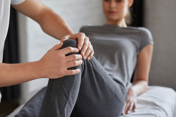 Female patient doing physical exercises with physiotherapist. Male therapist treating injured knee of young athlete.Post traumatic rehabilitation, sport physical therapy, recovery concept.