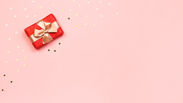 Creative Valentine's Day greeting card with red decorations and gift boxes, golden heart confetti on pink background, copy space, top view