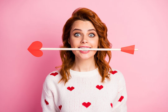 Close-up portrait of her she nice attractive lovely pretty cute amorous cheerful cheery funky childish wavy-haired girl angel holding in teeth arrow date isolated on pink pastel color background
