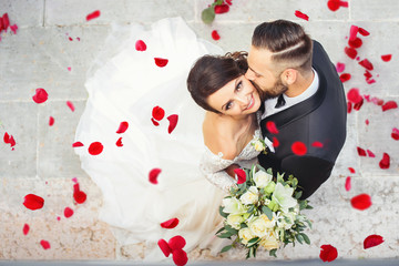 Beautiful wedding couple cuddling on their wedding day - it is raining roses