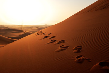 Footprints on the sand leading to sunrise in the desert for bright future concept
