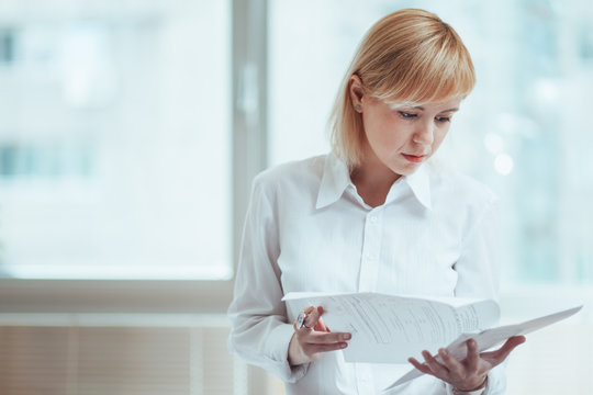 Woman in office, holding and reading documents